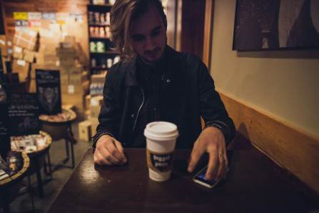 young man drinking takeaway coffee