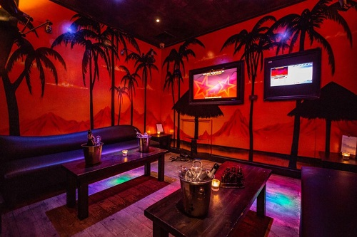 Karaoke room with leather pub seating and wooden pub tables