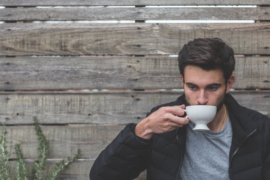 Young man drinking tea outside tea shop